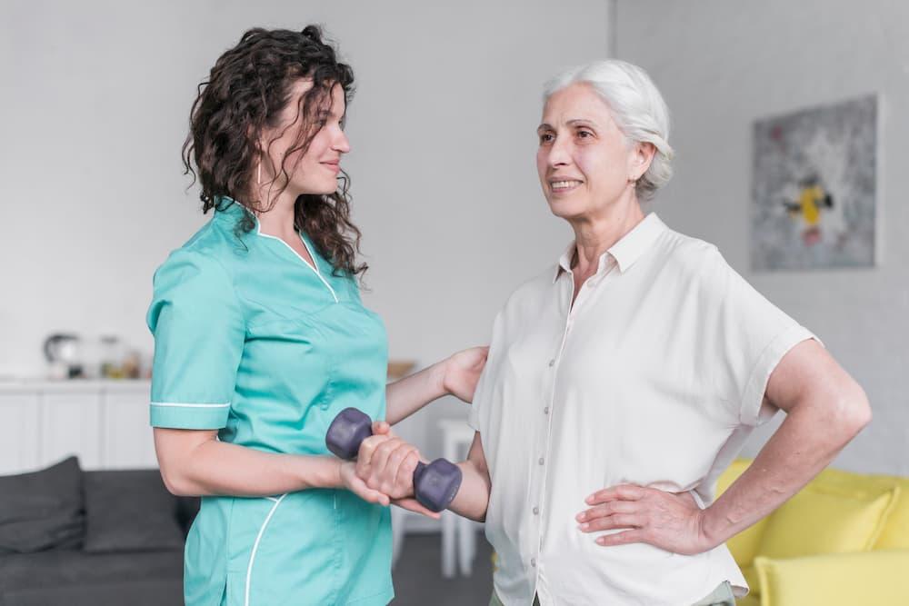 Fisioterapeuta acompanhando idosa